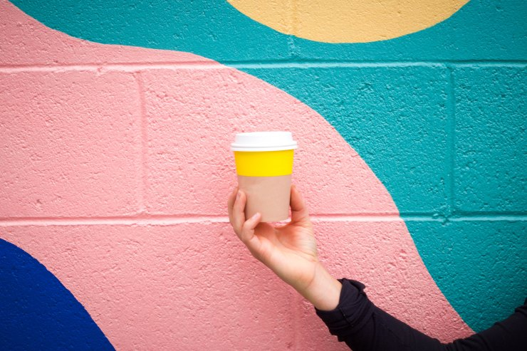 Bright yellow cup in front of pink wall