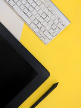 White keyboard and black tablet on yellow surface