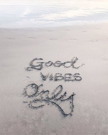 """Good vibes only"" written in the sand"