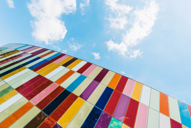 Colourful glass wall extending into the sky
