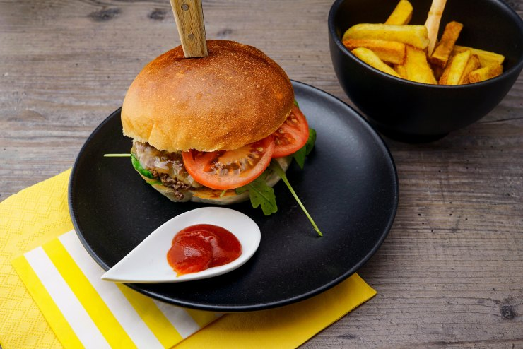 Burger, fries and ketchup on black plate