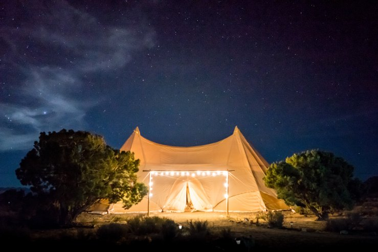 Lit tent and stars in the sky