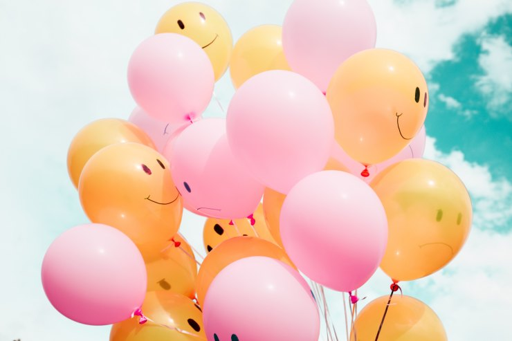Pink and orange balloons with happy faces