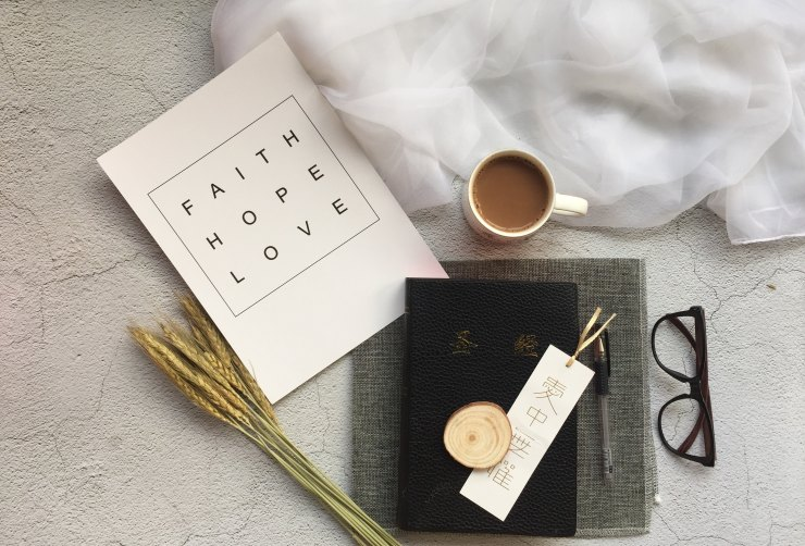 Faith-hope-love book next to coffee mug and glasses