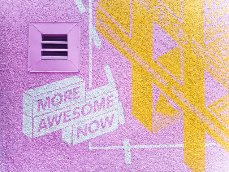 MORE AWESOME NOW MURAL on pink wall